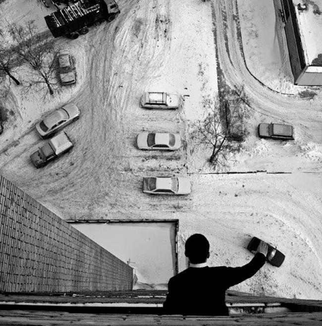 Hombre simula aparcar autos con su mano desde una terraza