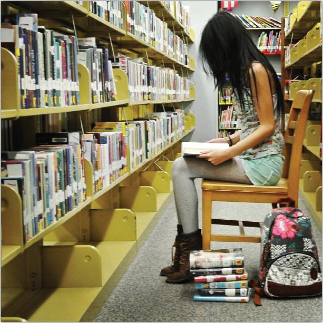 Joven lee en una biblioteca