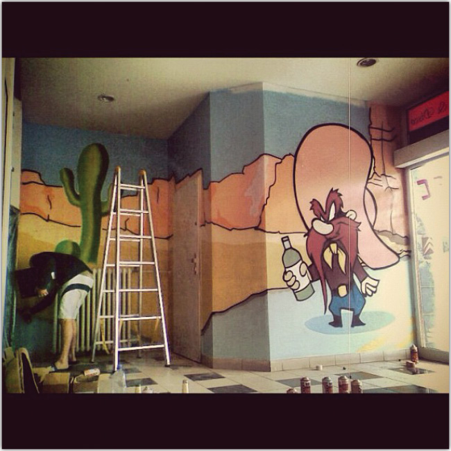 Hombre pinta la pared de un negocio