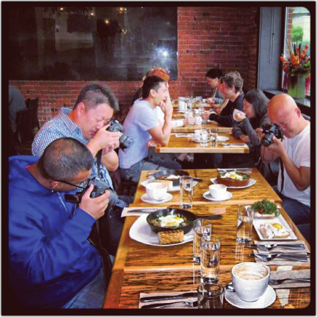 Turistas toman fotografías de sus alimentos en un restaurant