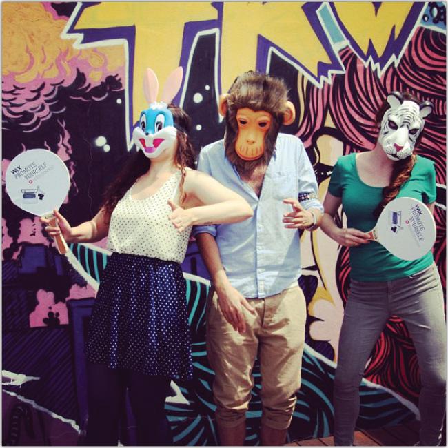 Dos mujeres y un hombre con mascaras de animales. Grafatti artistico en la pared de fondo.