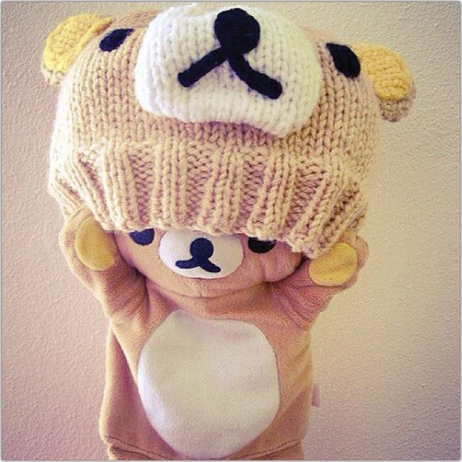 Oso de felpa usando un gorro de lana con cara de oso de felpa.