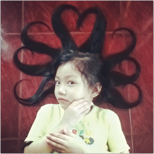 Niña acostada en el piso con su pelo formando 6 curvas y 1 corazón.