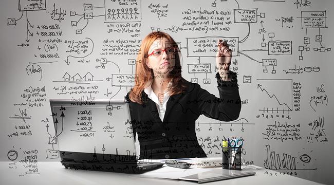 Mujer ejectuiva sobre su escritorio escribiendo sobre una pizarra transparente.