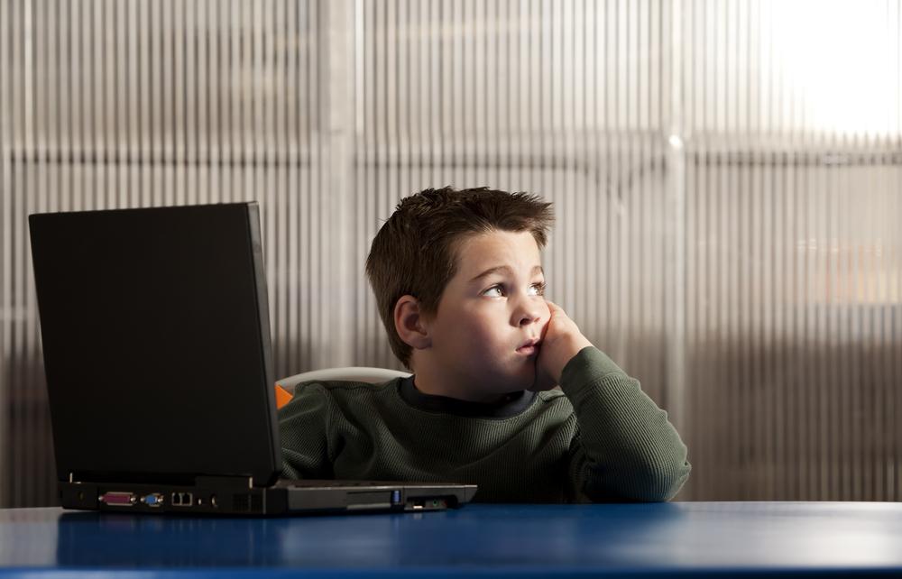 Niño frente a un computador y con cara de aburrimiento.