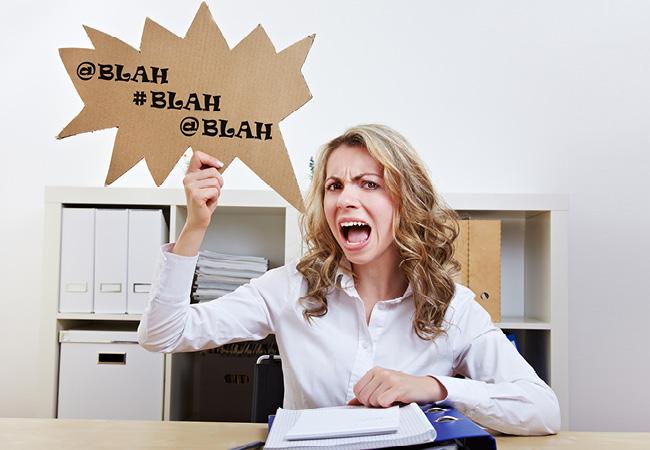 """Mujer sentada en un escritorio, gritando y con un cartel tipo """"globo de cómic"""" que dice """"blah blah blah"""""""