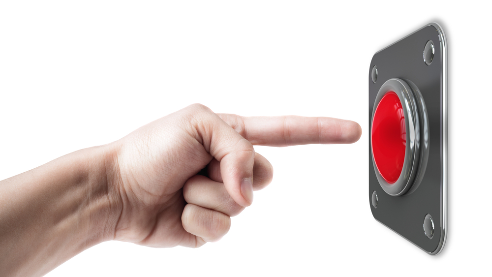 Dedo indice a punto de presionar un botón rojo.