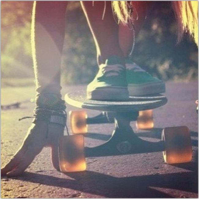 Primer plano de los pies de una mujer sobre una tabla de skate en movimiento