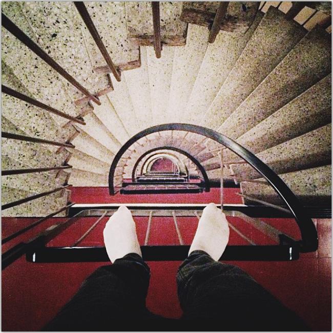 Pies mirados desde arriba con una enorme escalera de caracol abajo de ellos. Imitando un salto a suceder.