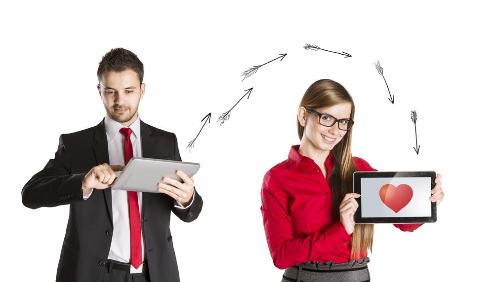 Hombre y Mujer coqueteando el uno con el otro a través de sus tablets