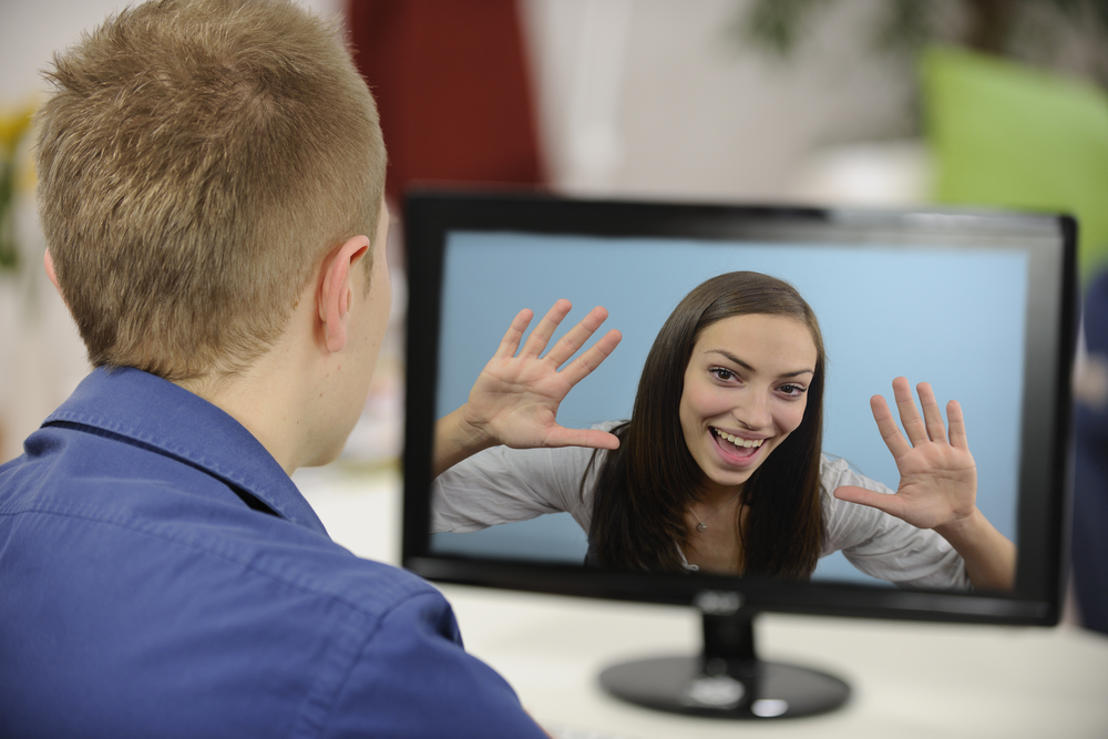 Hombre de espalda mirando la pantalla de un computador, desde donde una mujer lo saluda.