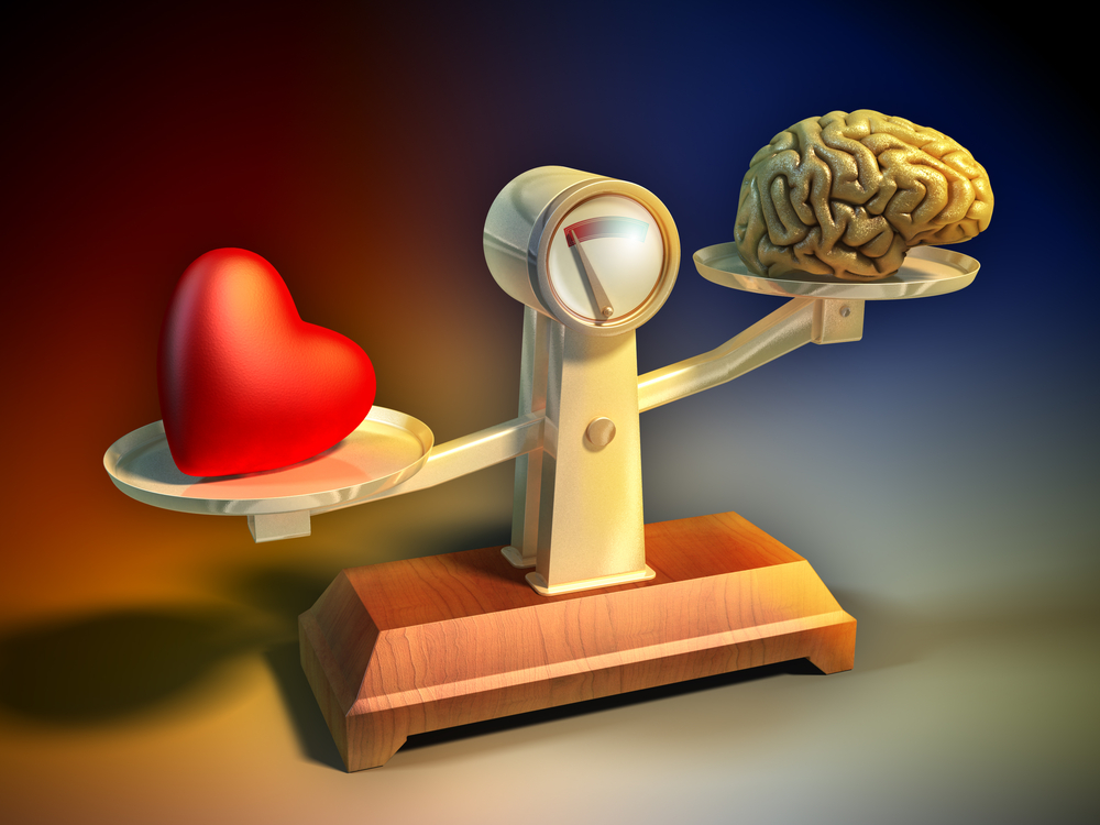 Balanza antigua donde hay un corazón y un cerebro. El corazón pesa más, inclinándose la balanza hacia él.