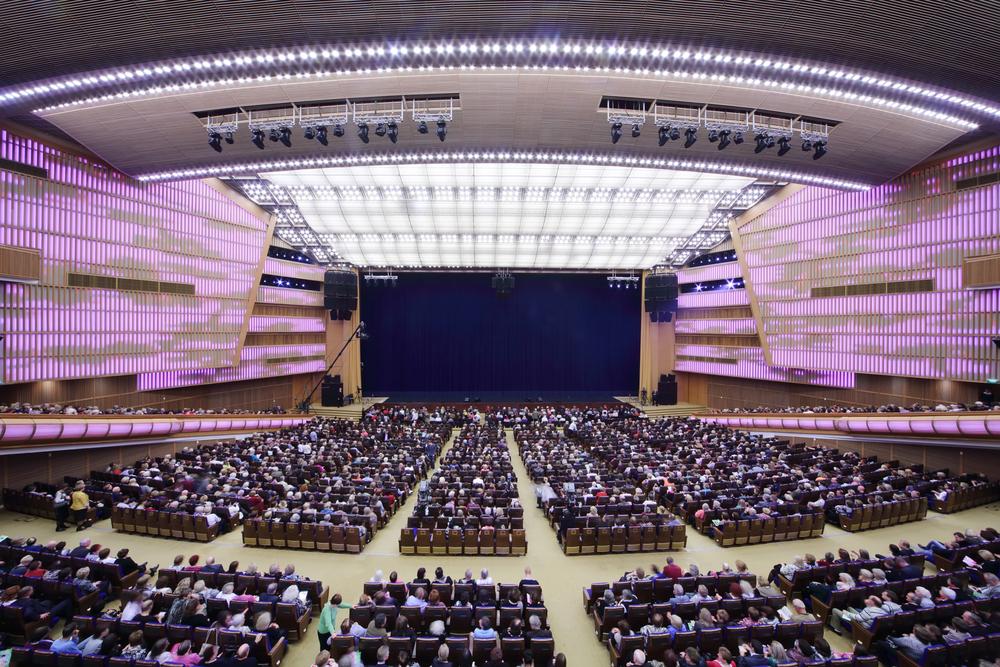 Teatro lleno. Audiencia repleta y escenario vacío. Vista desde atrás de la audiencia.