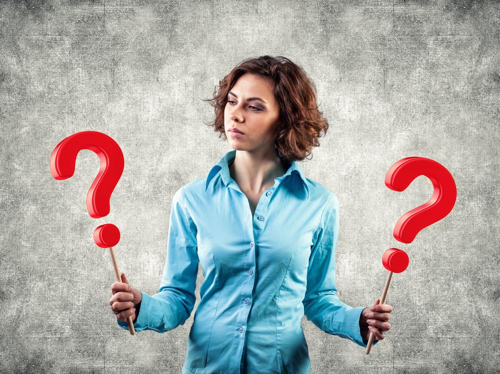 Mujer sosteniendo dos signos de interrogacion. Uno en cada mano.