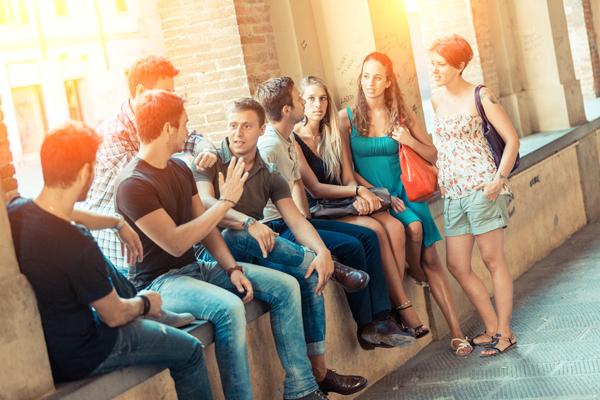 Grupo de jóvenes sentados y compartiendo en una especie de terraza en el atardecer