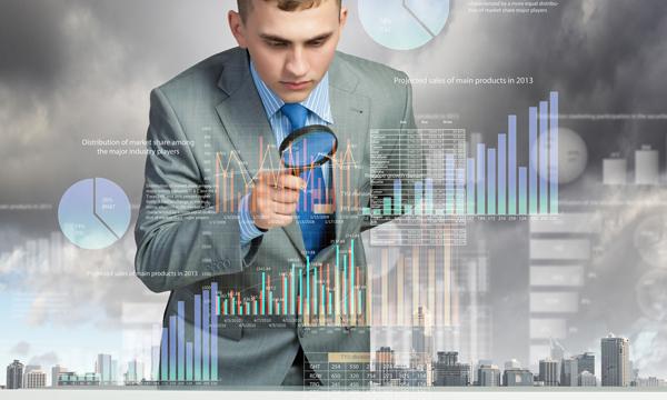 Hombre con una lupa analizando gráficos que están en formato de holograma