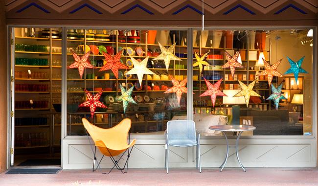 Imagen de una tienda con una vitrina colorida y dos sillas fuera de la tienda