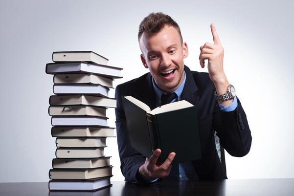 Hombre leyendo un libro y levantando el dedo índice con una expresión de felicidad en su rostro