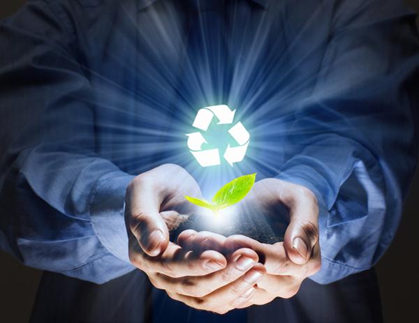 Manos de un hombre sosteniendo tierra y el símbolo internacional del reciclaje iluminado
