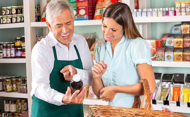 Un vendedor de supermercado mostrándole un producto a una clienta sonriente