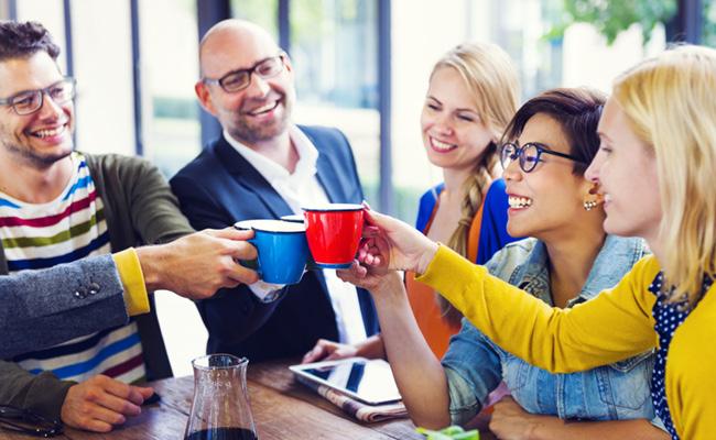 Grupo de personas felices brindando con tazas de café