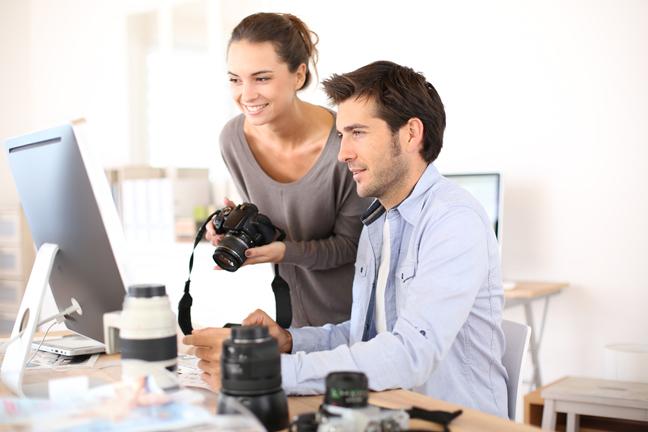 Dos fotógrafos traspasando las fotos desde sus cámaras a sus computadores