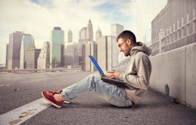 Muchacho sentado en la calle con laptop en la falda