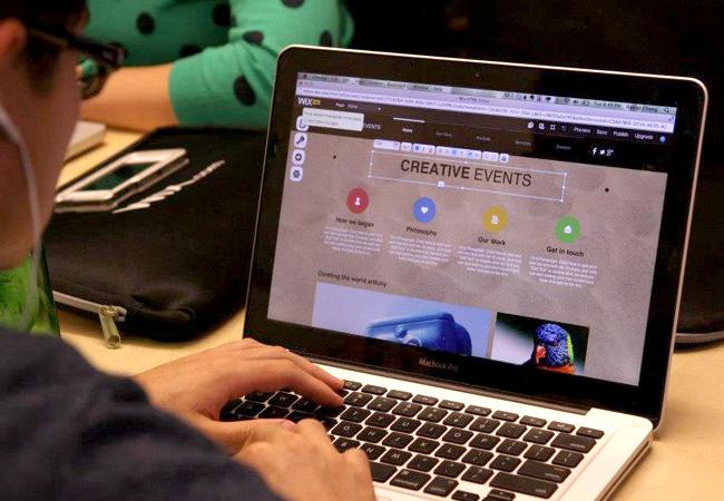 Joven crea un sitio para eventos en laptop