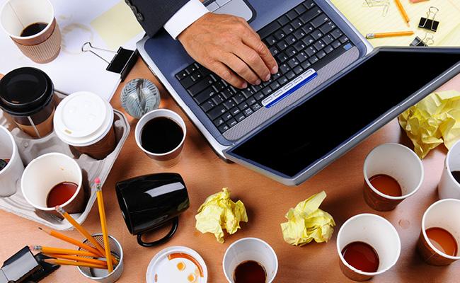 Computador rodeado de tazas de café usadas