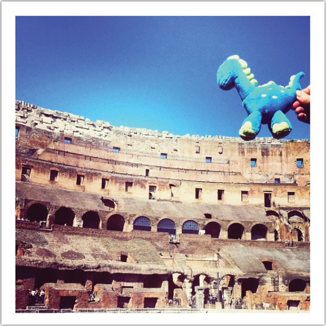Juguete de dinosaurio caminando sobre ruinas Grecoromanas.