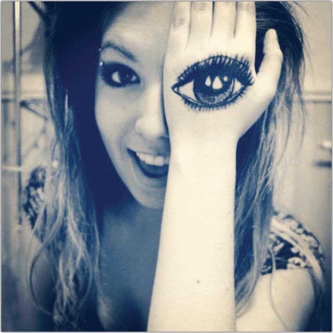 Muchacha Joven con la mano sobre el ojo y un ojo grande dibujado sobre la mano.