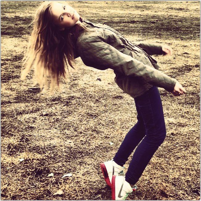 Muchacha joven en punta de pies en medio de un terreno vacío.