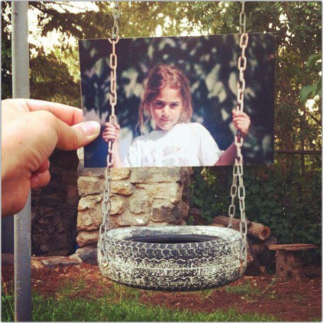 Foto impresa de una niña en un columpio, sobrepuesta sobre el columpio real.