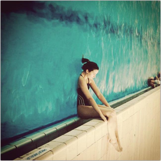 Imágen rotada de una mujer entrando de espaldas a una piscina. En la imágen, el agua parece una pared.