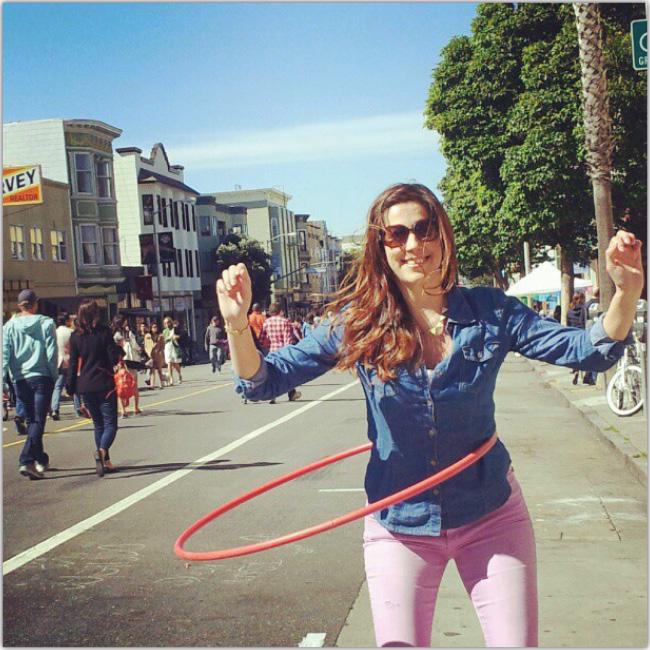 Muchacha joven jugando con un aro de ula en su cintura en medio de una feria en la calle.