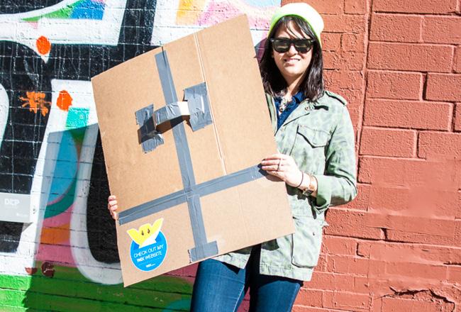Mujer posando con una caja de cartón con el Sticker de Wix en ella.