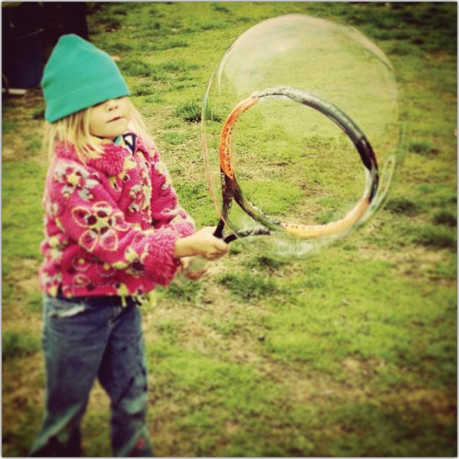 Niña pequeña haciendo una burbuja gigante