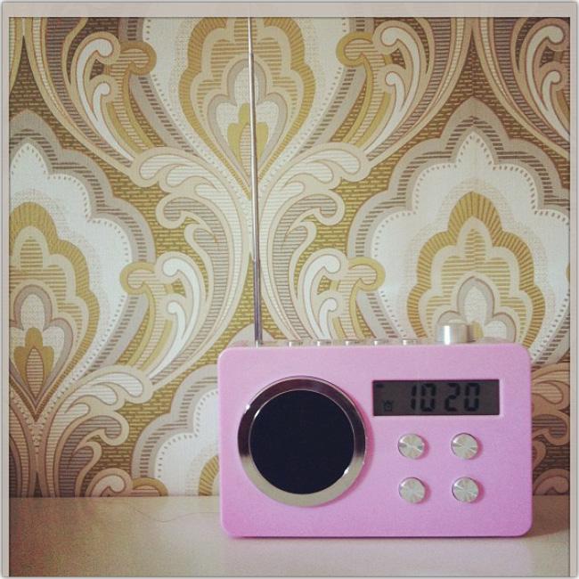 Radio antigua con antena metálica de color rosado en primer plano.