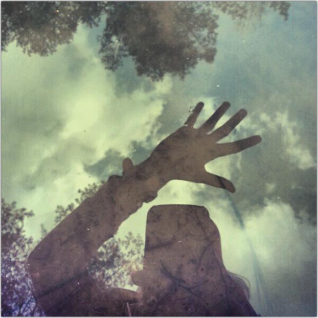 Silueta de una persona con la mano extendida y sobre su cabeza