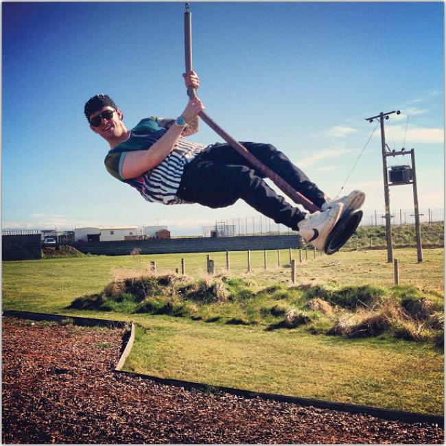 Hombre en un parque balanceandose en una cuerda que cuelga.