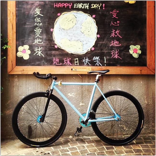Bicicleta celeste bajo una pizarra con un dibujo chino.