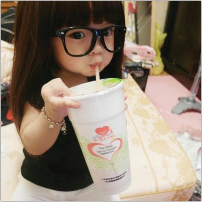 Pequeña niña oriental con anteojos bebiendo desde la bombilla de un vaso grande.