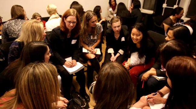 Sheryl Sandberg rodeada de mujeres y hablando sobre su libro
