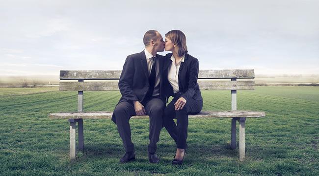 Pareja de ejecutivos besándose en un banco en medio de un área verde