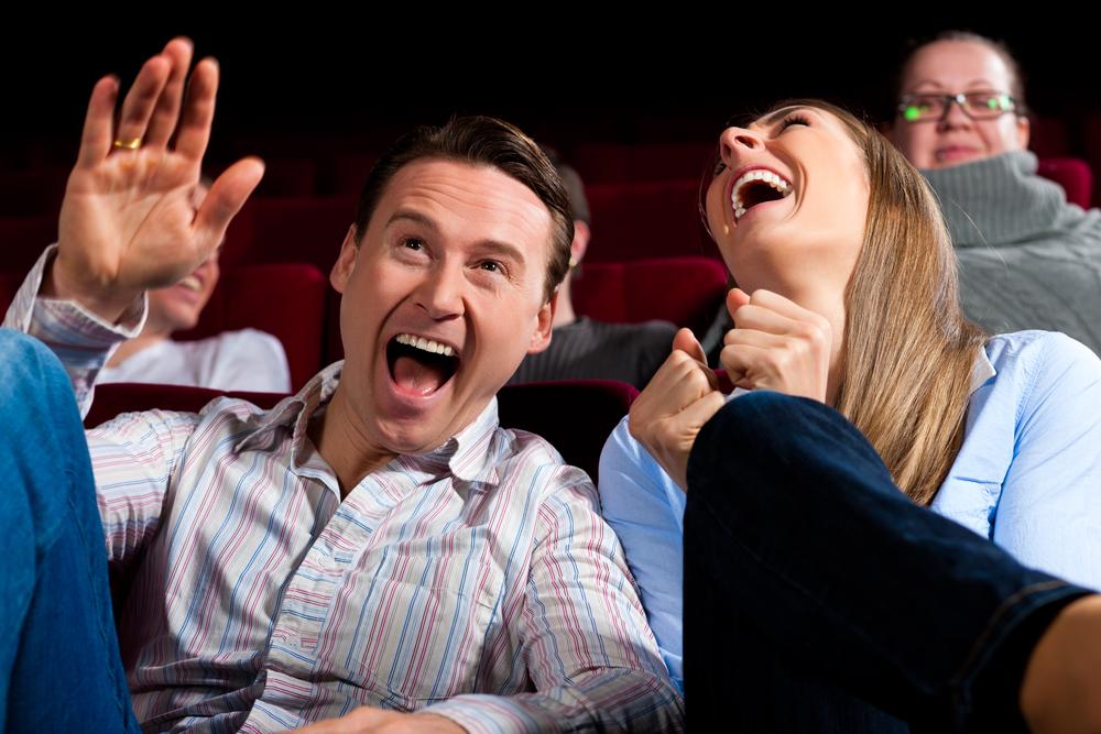 Hombre y mujer en el cine, riendo a carcajadas.