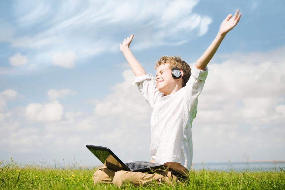 Niño con audifonos inalambricos y computadora en medio de un parque