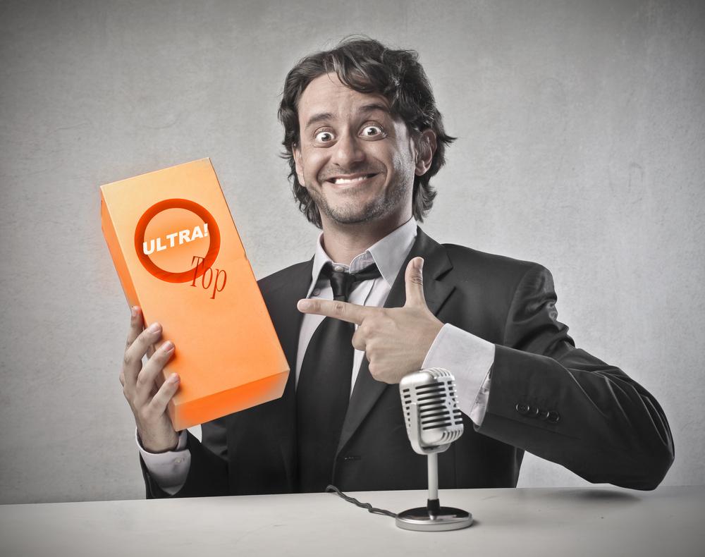 Hombre sosteniendo un producto en una caja naranja y sonriendo de forma irónica