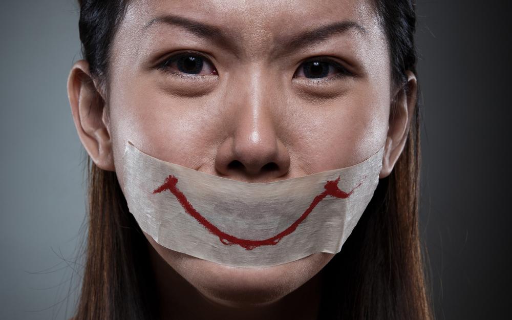 Mujer con una cinta adhesiva en su boca con una sonrisa dibujada en ella