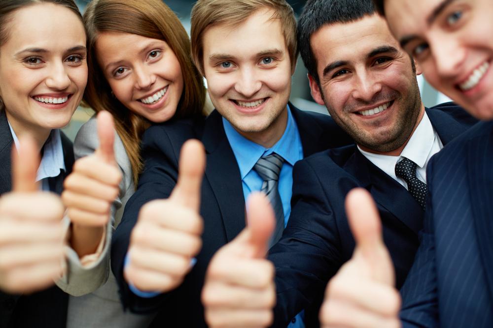 Un grupo de ejecutivos sonriendo con el dedo pulgar arriba