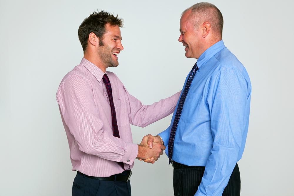 Dos oficinistas dandose un apretón de manos y un pequeño abrazo.